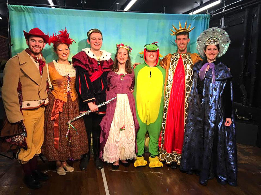 six performers in bright, fanciful costumes, including one dressed like a dragon.
