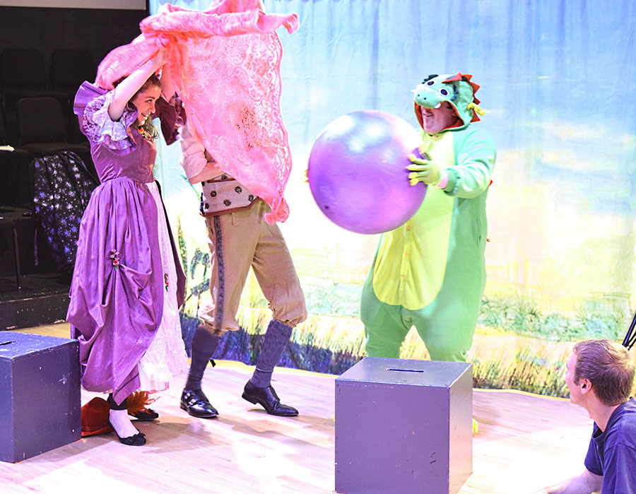 two brightly clothed actors flail about near person in dragon suit holding purple ball.