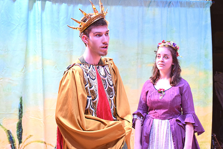 actor with crown orates while actor in purple dress attends