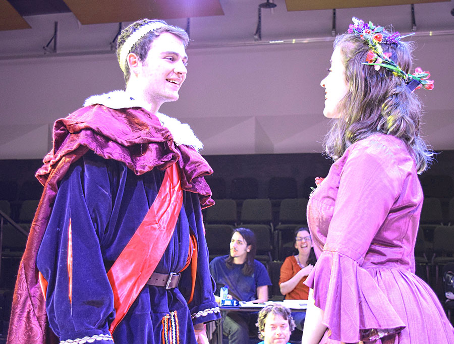 actor dressed as king converses with actor in purple dress