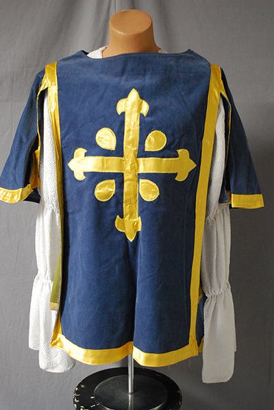 Blue smock over white blouse. Smock embellished with gold cruciform insignia (ala Three Musketeers)