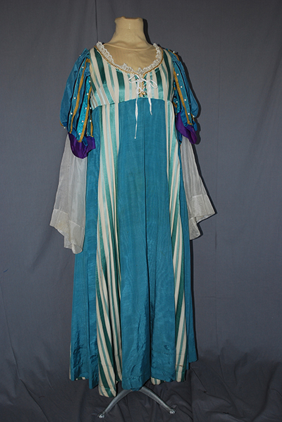 blue, green, turquoise panels and striped dress with diaphonous demi-cape. Low neckline.