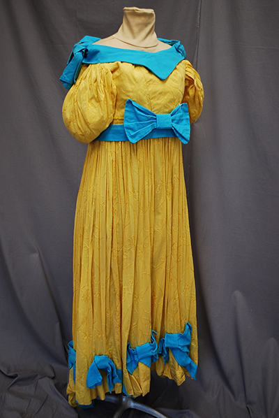straw colored gown with demi-gigot sleeve, large blue bow at waist, matching dress collar. matching small bows at hem.