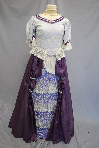 simple dress with fitted white bodice, high neck, mid-length sleeves, purple skirt with revealed panel of lavendar lace.