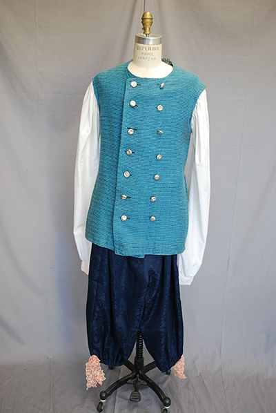 Light bluse double breasted waistcoat with silver buttons. Black pantaloons.