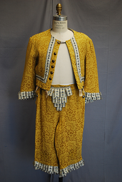 Short patterned gold jacket with matching broad breeches. All trimmed with fabric tassles.
