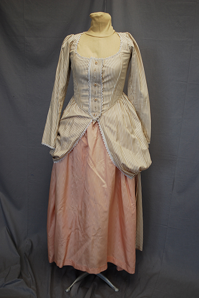 Cream colored fitted jacket with low neckline and peuplum over light rose ankle-length skirt