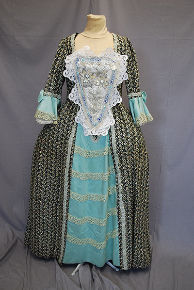 patterned grey/green dress with lace stomacher, flared sleeves of light bliue, light blue panel in front of skirt.