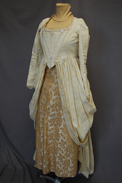 cream colored casaquin. full length sleeves, long peplum, patterned coordinate skirt.