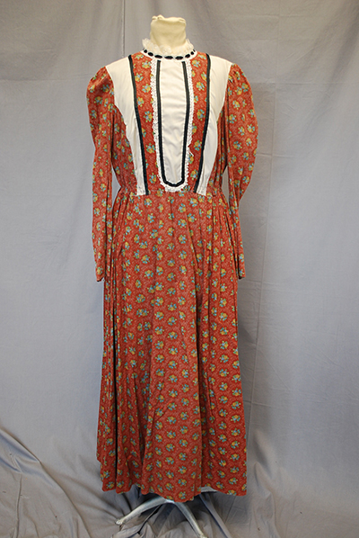 Prairie dress. Rust-colored with small floral design. White accents on bodice.