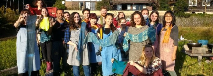 A group of students posing, each holding out a shibori dyed scarf