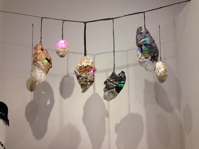 Cocoon-like figures hanging from a string