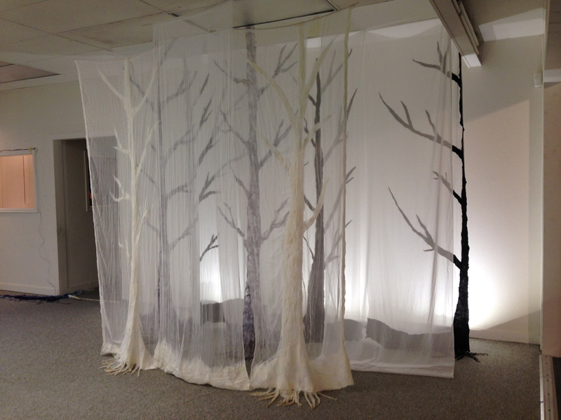 Sheer curtains hang in front of tree silhouette cut-outs
