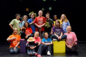 Thirteen students on stage in brightly colored MOTley t-shirts