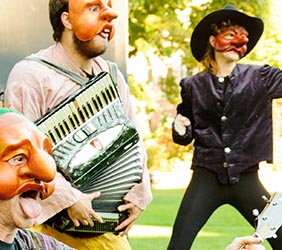 Three actors wearing big-nosed masks in a park, one yields an accordion