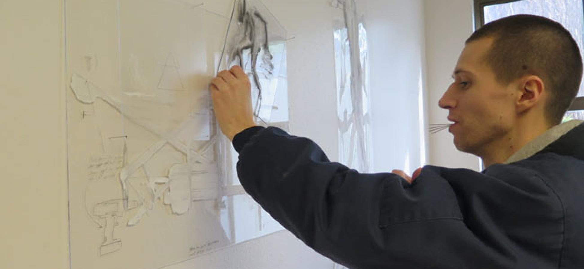 A student working on a drawing on the wall