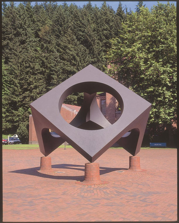 outdoor sculpture of a 3 sided, 3D square structure resting on its corners on legs. Each square side has a large round hole punched out of it