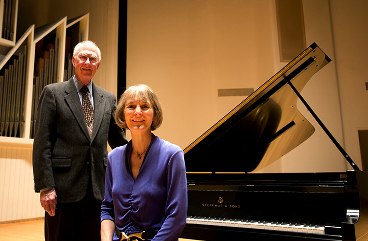 An elderly man and woman next to a Steinway piano