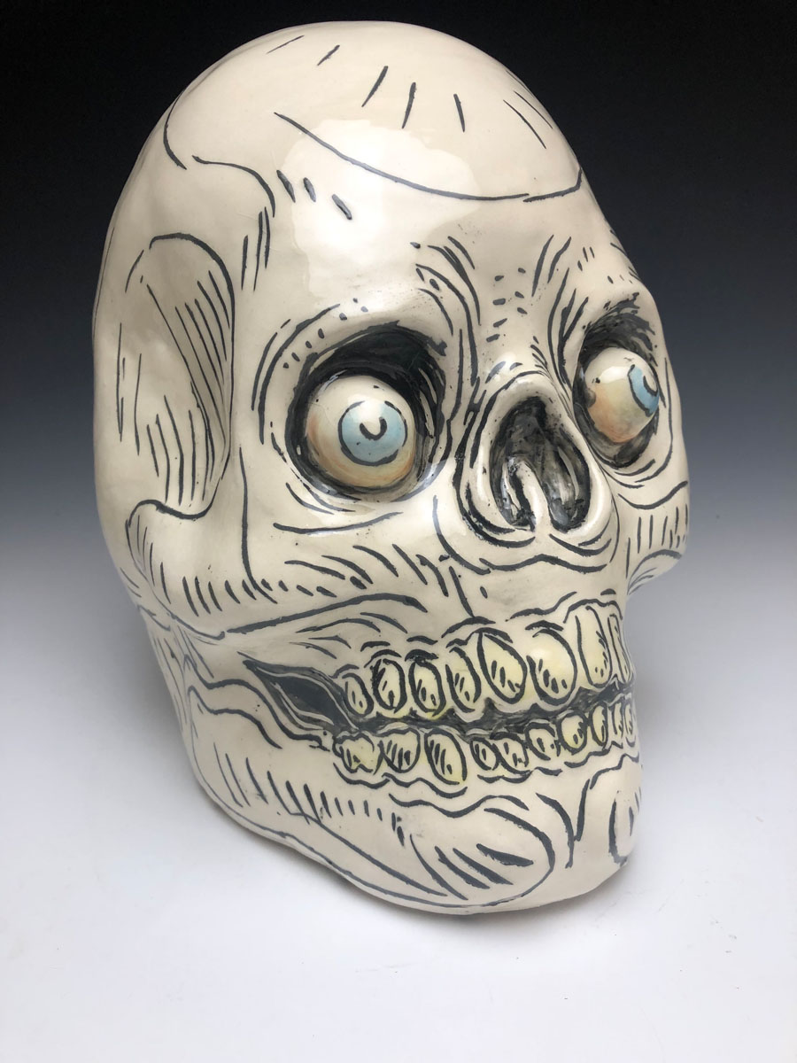 ceramic skull painted with fine lines. It has bulging eyes in the sockets