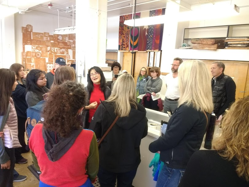 people talk in a crowded fiber arts studio