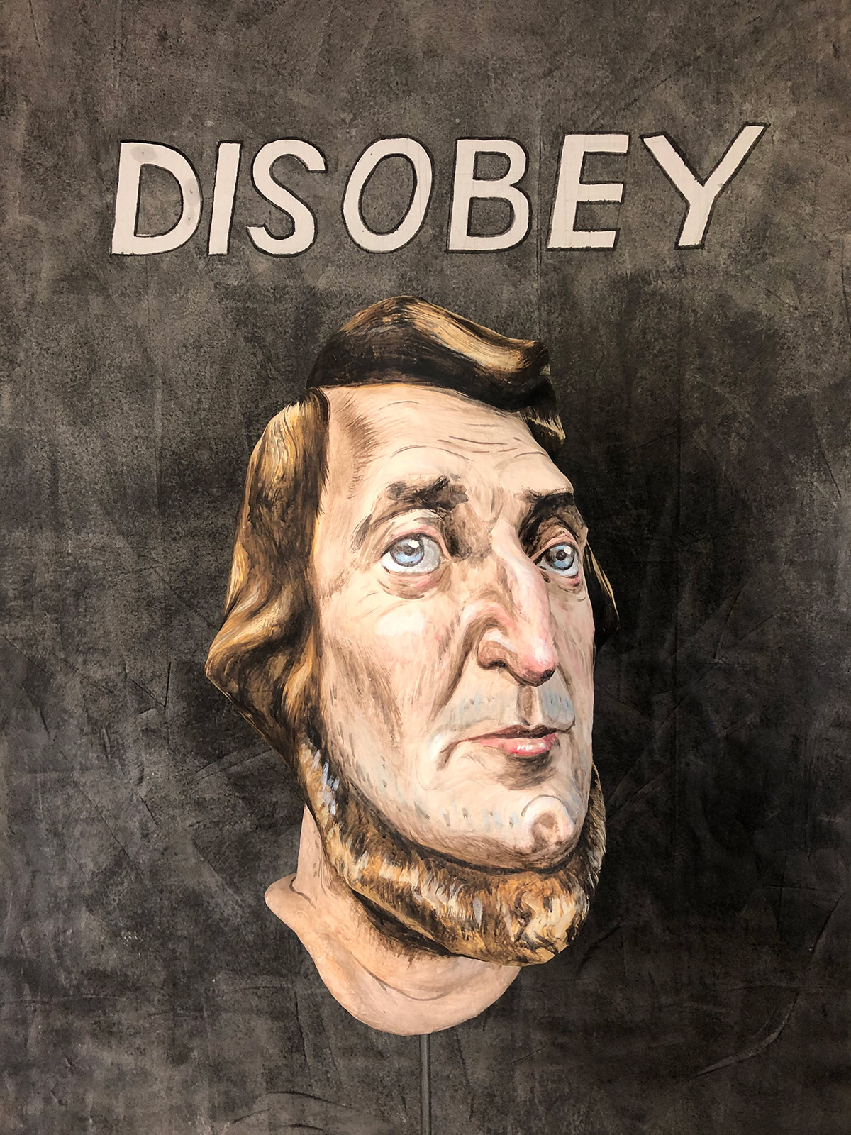 papier mache bust of Thoreau with the word disobey printed on fabric over the bust