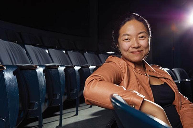 theatre director in tan leather jacket sitting in audience seats