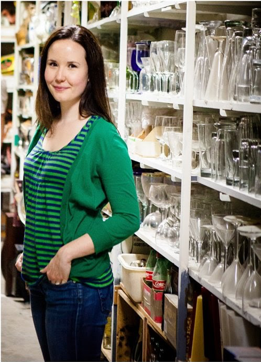 woman in green cardigan in front of shelves full of glassware
