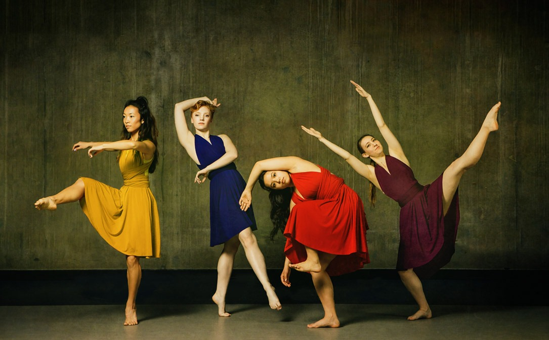 four dancers in solid color costumes pose dynamically