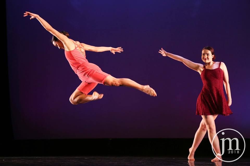 a dancer flies through the air, looks like she's been tossed by a second smiling dancer