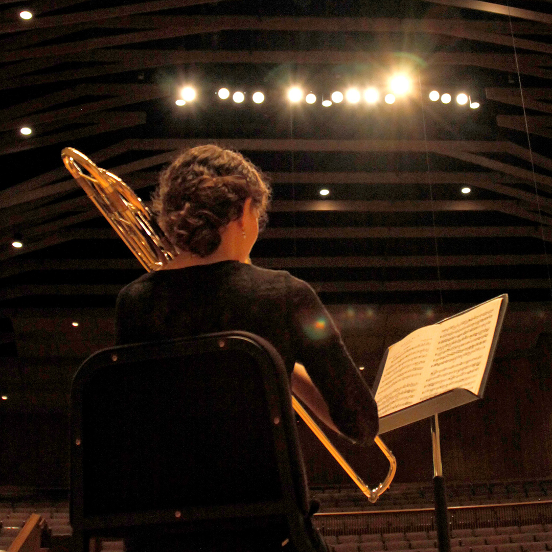 view from behind a student playing an instrument on stage in the Western's Concert Hall