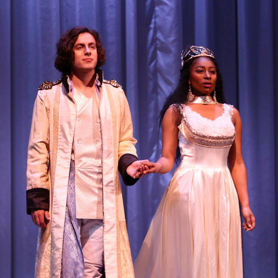 Two people on stage in formal wear, holding hands, looking regal