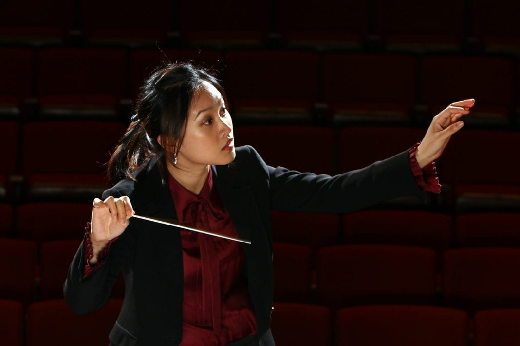 A person in formal attire focuses holds one hand out with a focused gaze in that direction, and the other hand holds a conductor's wand