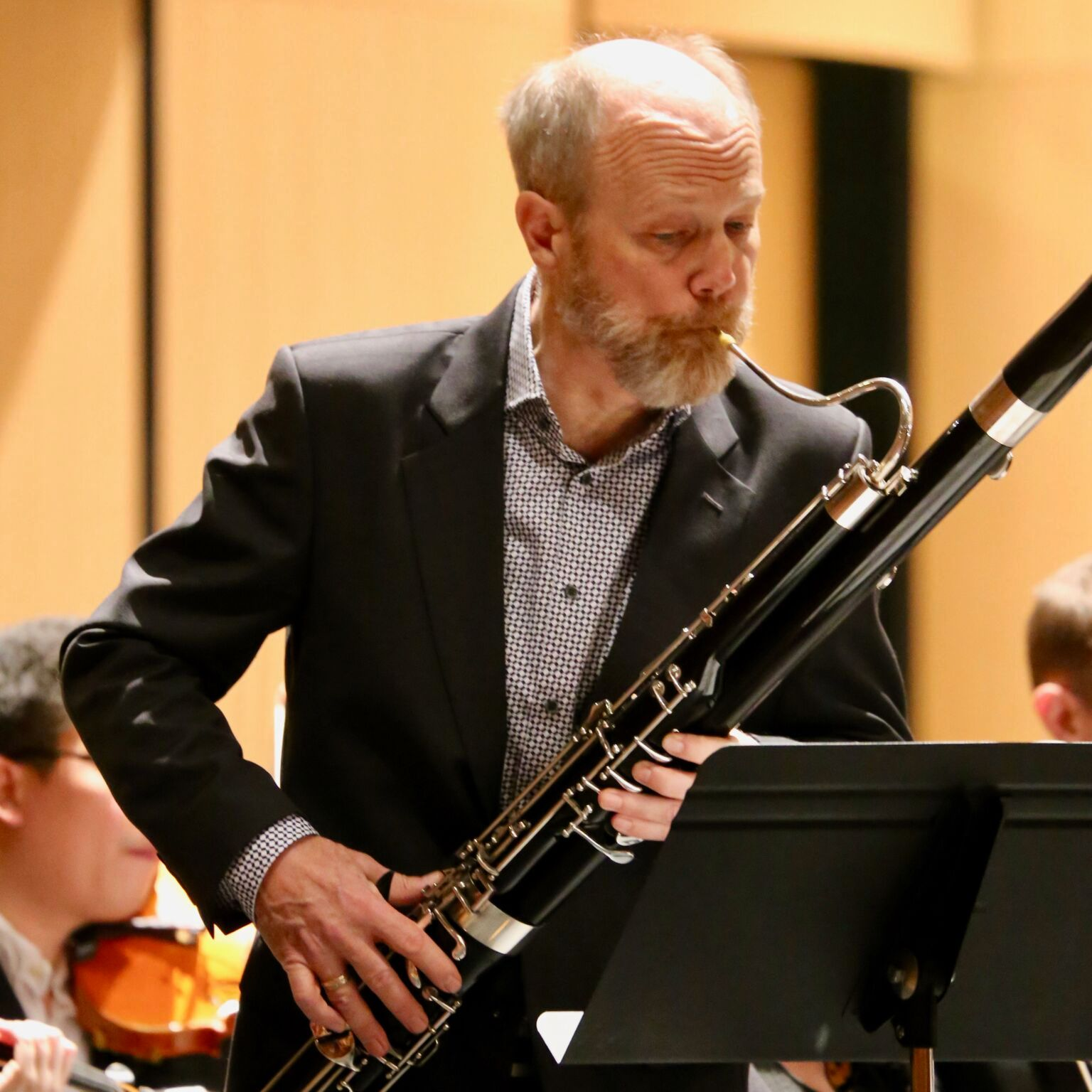 man with beard blows into a bassoon