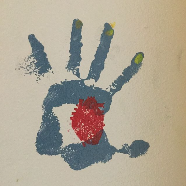 blue handprint with an anatomically correct red heart painted into the palm