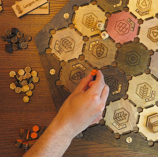 a game made of hexagonal wood tiles with woodburned designs on them
