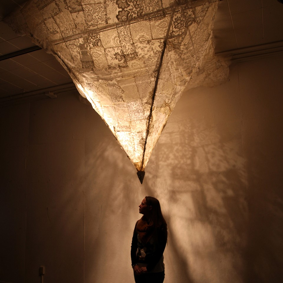 A silhouetted person stands looking up at the bottom point of an inner-lit, triangular hanging sculpture