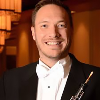 Dr. Andrew Parker in a tux, with a big smile, holding an oboe