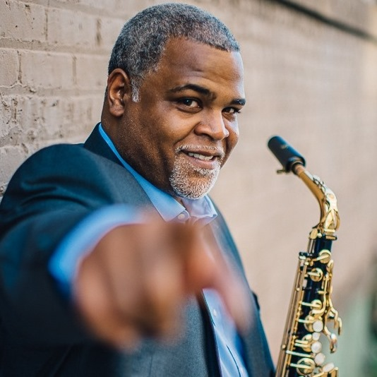 Gray-haired person with a well-groomed beard and a saxophone smiles and points at the camera