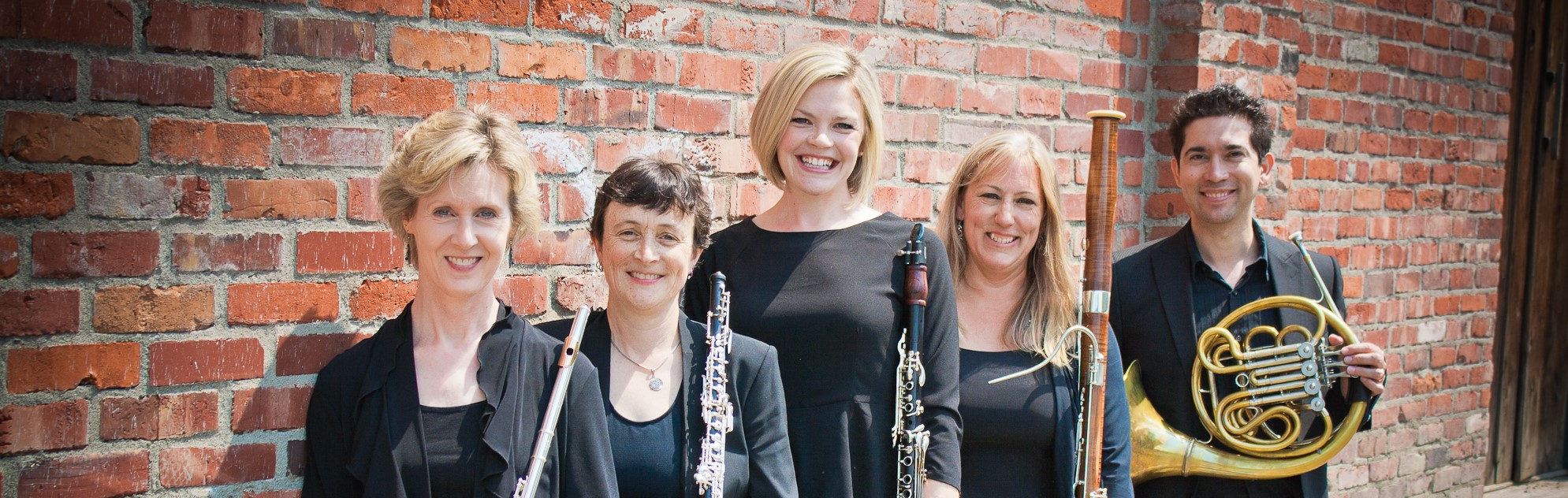 Fifth Inversion ensemble members standing together in front of a brick wall, holding instruments and smiling