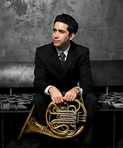 Gustavo Camacho holds a french horn