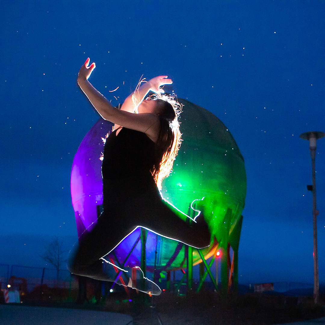 A backlit dancer leaps high and arches back with arms and legs curled. In the background is the colorfully-lit acid ball from the Bellingham waterfront park, under a starry night sky.