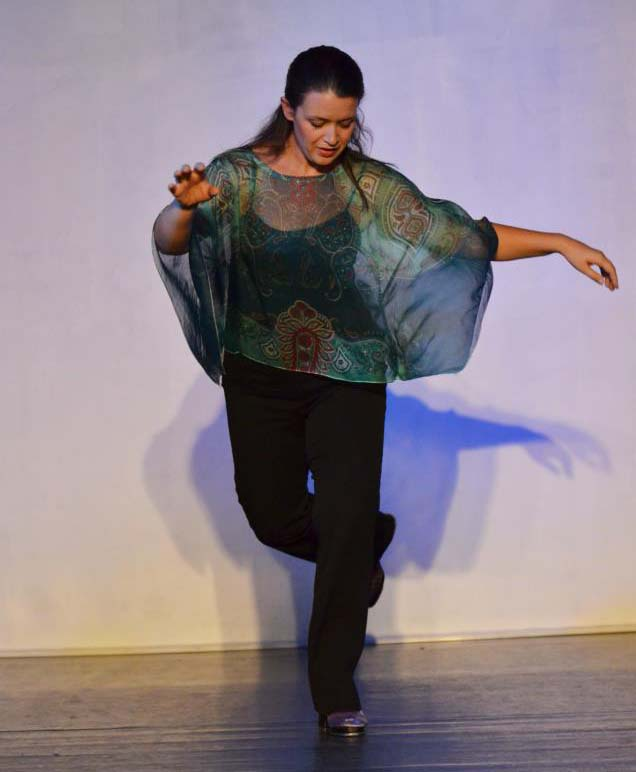 a dancer in a graceful pose wearing a diaphanous green shawl
