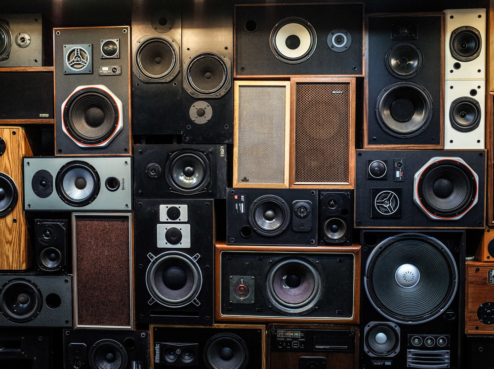a wall of various audio speakers all stacked together, with the woofers and the tweeters visible.
