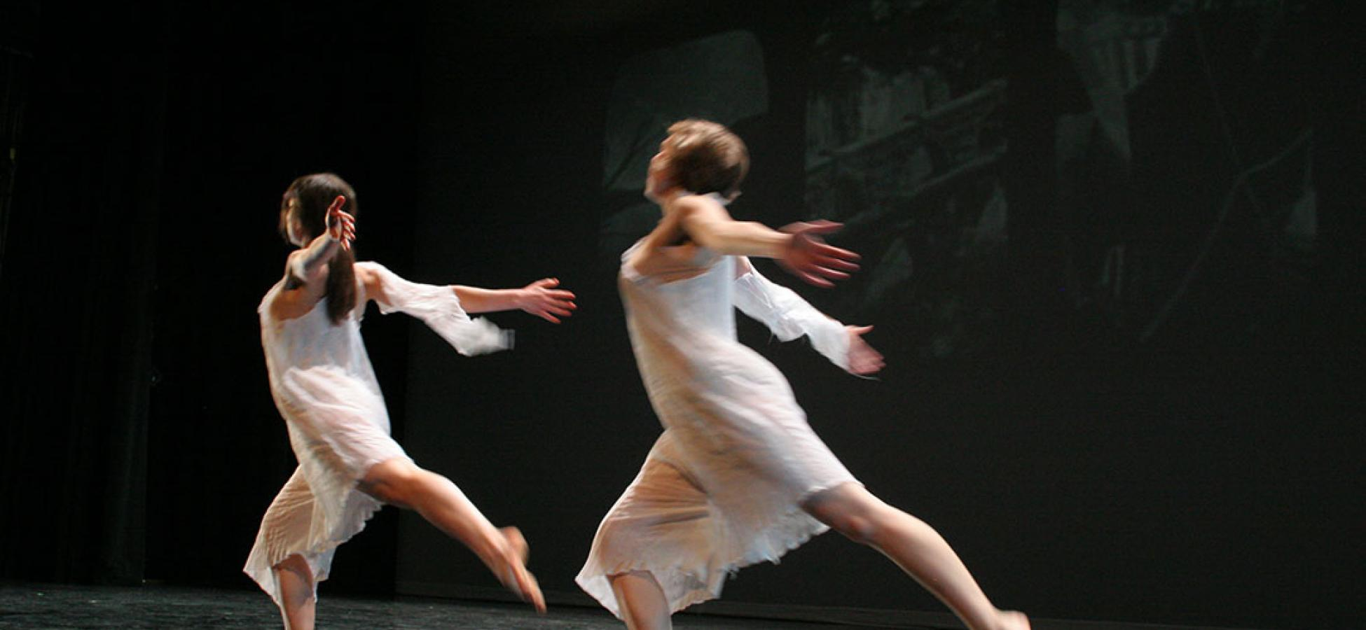 two dancers in white swooping leftward on black stage