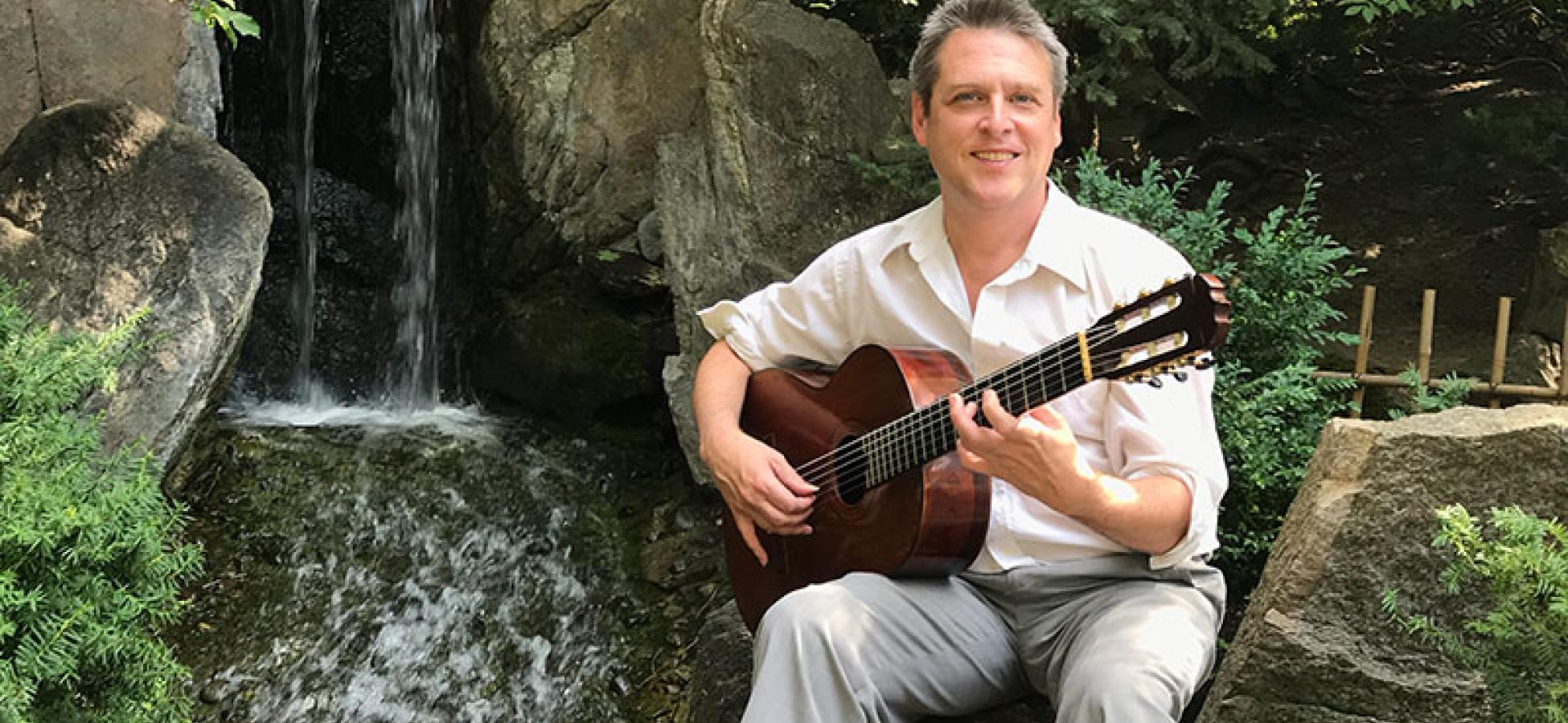 Paul Grove seated in natural setting with guitar