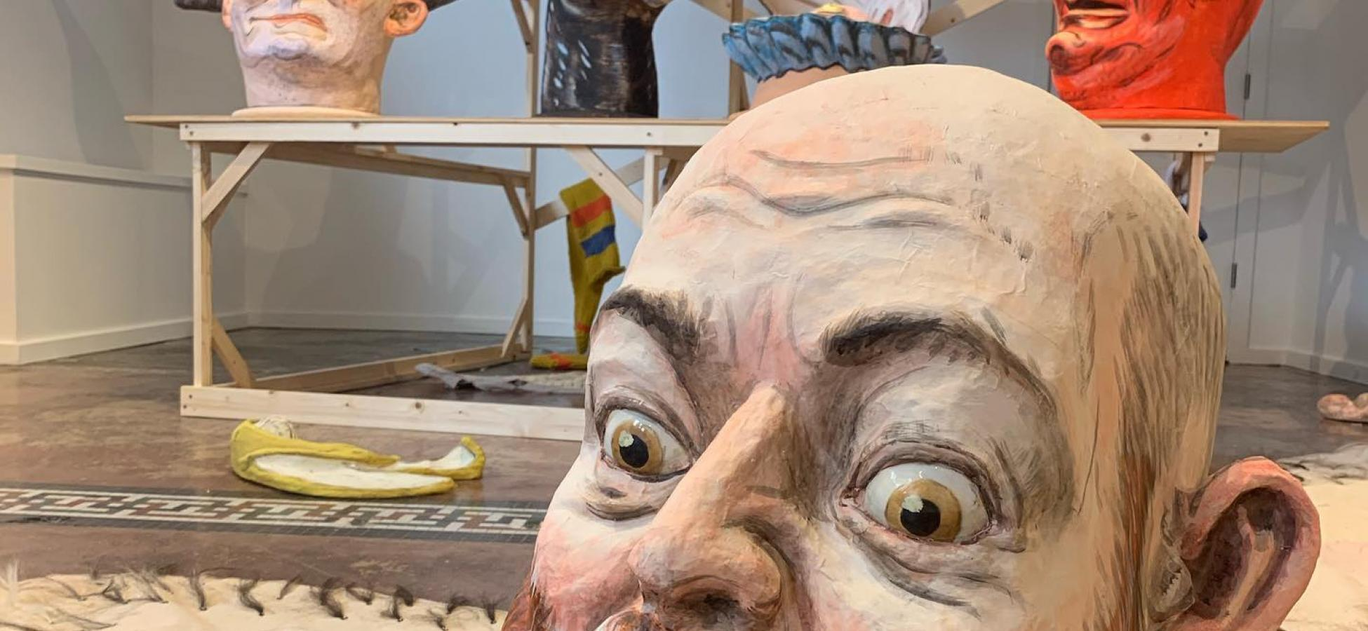 A giant head of Ryan Kelly. Behind are carnivalesque caricatures of animals, demons, witches