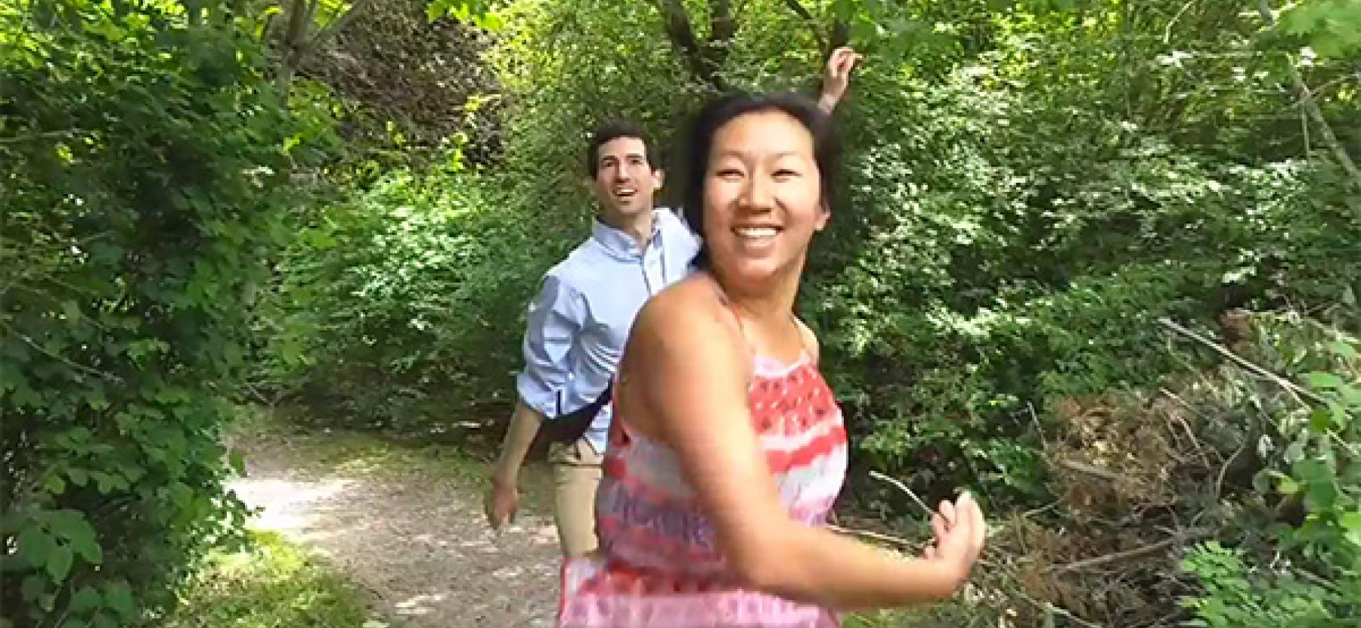 two dancers in a park setting dash smiling toward the camera
