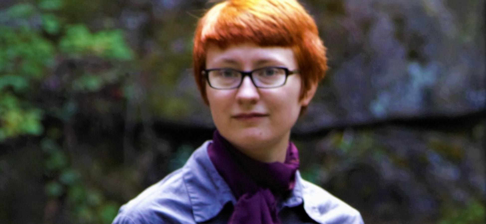 young person with short red hair and a dapper purple shirt and scarf