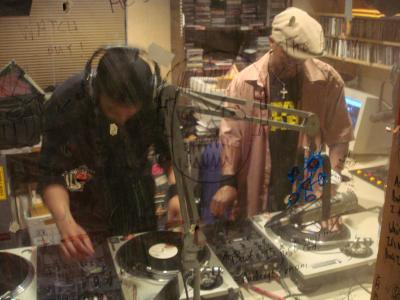 Two hip hop DJs creating new music by mixing tracks from multiple record players
