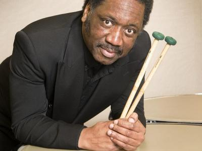 Michael Crusoe in a snazzy formal suit, holding drumsticks in his hands while leaning his elbows on a large drum and looking up at the camera